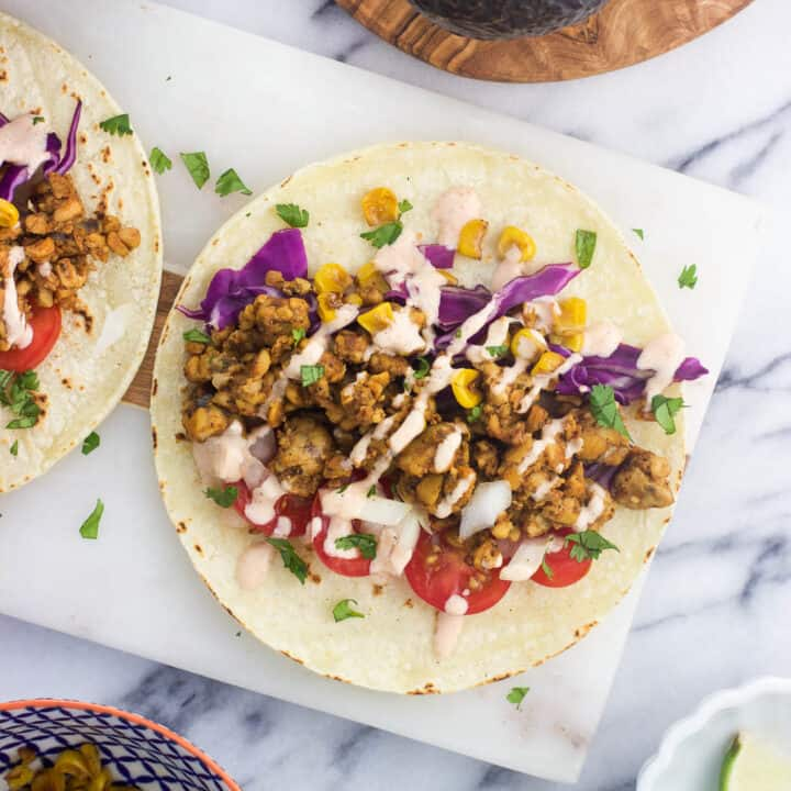 An overhead shot of assembled tempeh tacos featuring tomatoes, cilantro, a spicy non-dairy yogurt drizzle, roasted corn, onions, cabbage, and more.