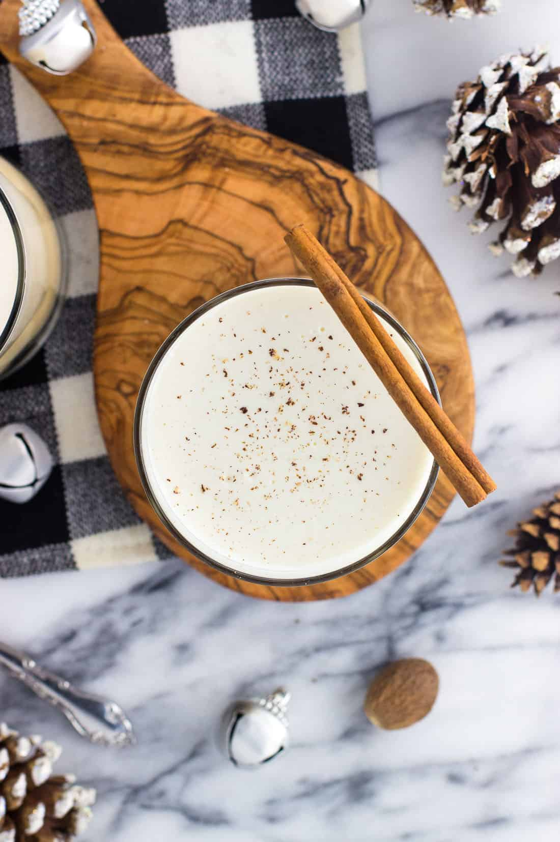 An overhead shot of a glass of eggnog dusted with grated nutmeg and garnished with a cinnamon stick