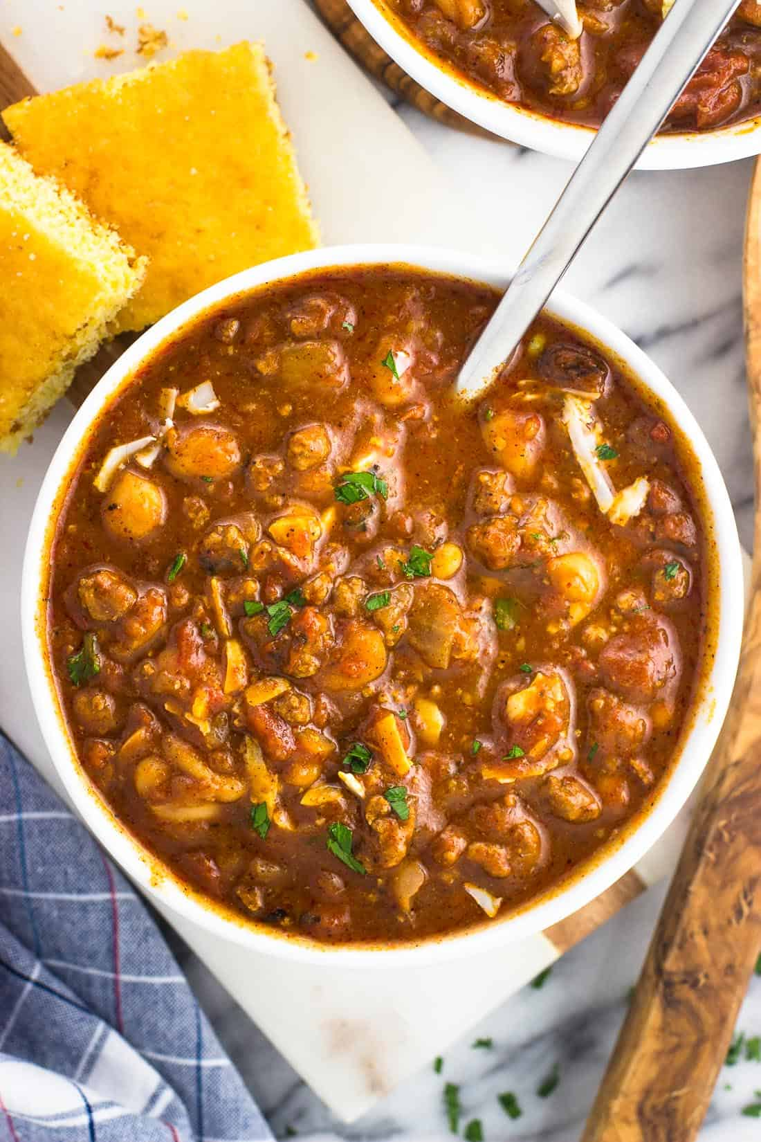 A bowl of turkey chili next to pieces of cornbread