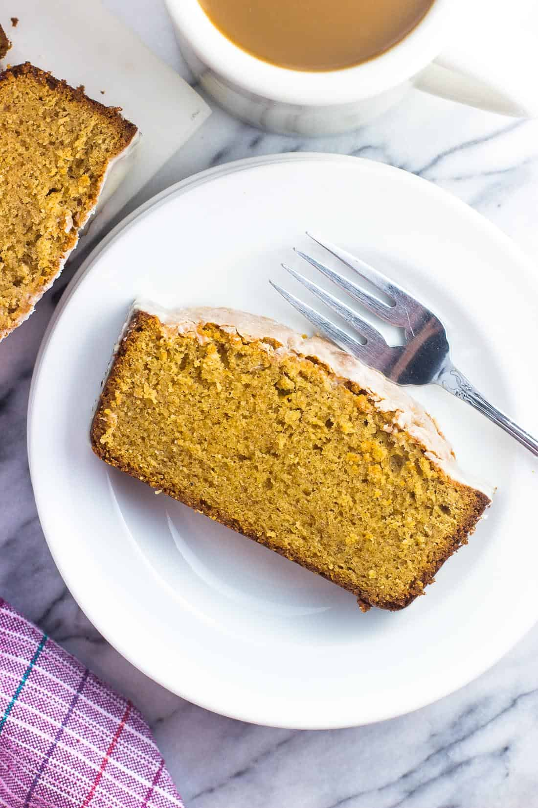 A slice of vanilla chai pound cake on a cake plate with a fork