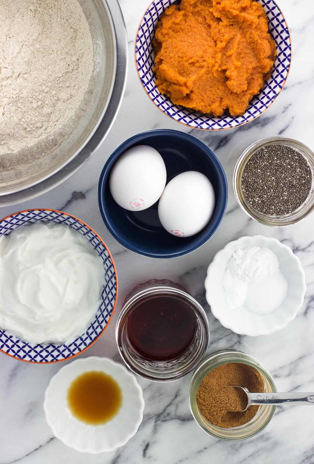 An overhead shot of healthy pumpkin muffin ingredients in separate bowls on a marble board