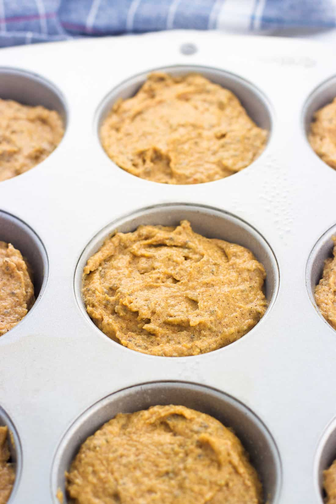 Unbaked pumpkin muffin batter portioned out in a metal muffin tin