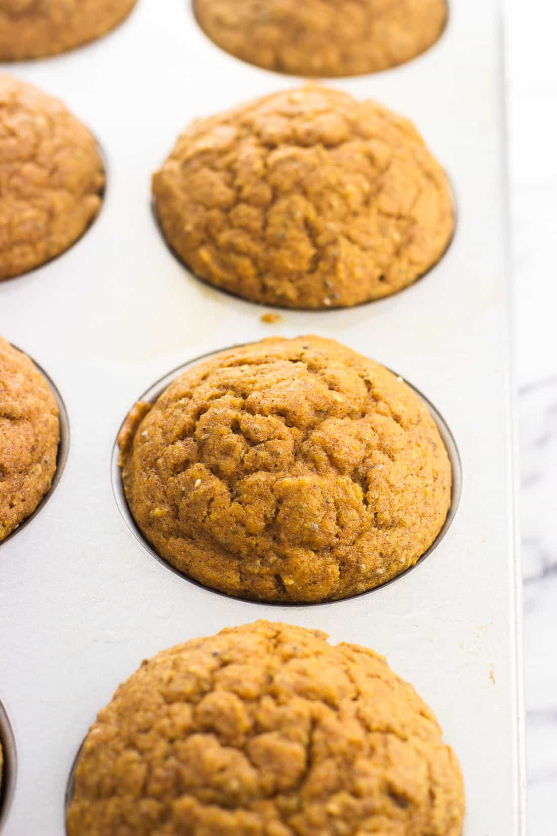 Baked pumpkin muffins in a metal muffin tin