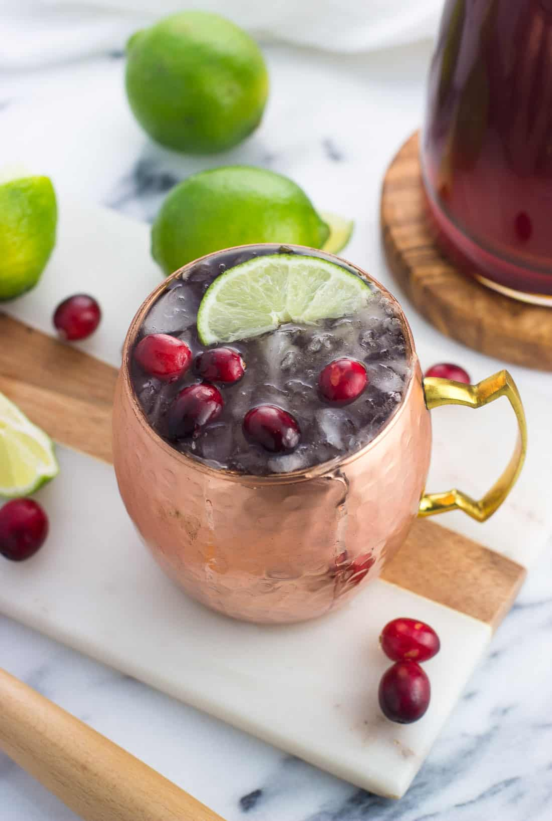 A cranberry moscow mule in a copper mug garnished with a lime wedge and fresh cranberries