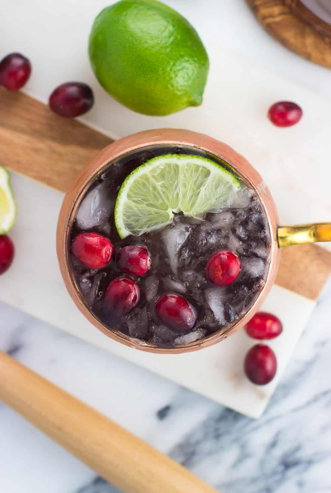An overhead shot of a cranberry moscow mule in a copper mug on a marble serving tray