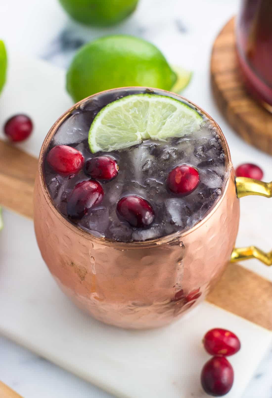 A cranberry moscow mule cocktail in a mug on a marble serving board surrounded by fresh cranberries and limes