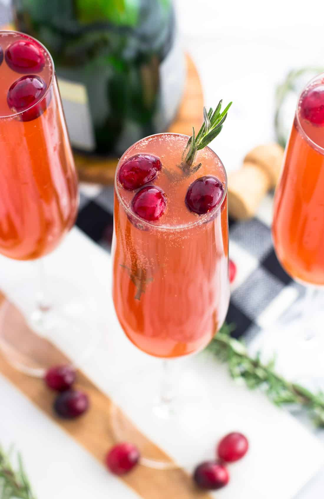 Three cranberry mimosa cocktails in champagne flutes garnished with a sprig of rosemary and fresh cranberries