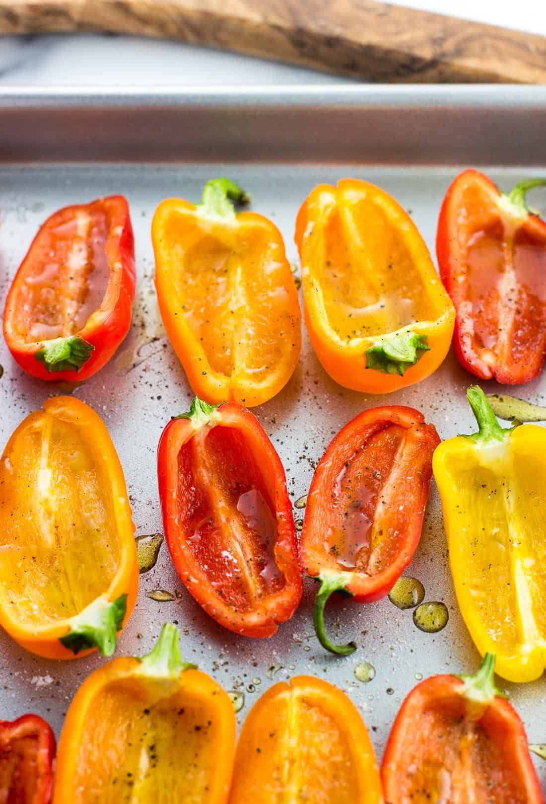 Roasted mini sweet pepper halves on a baking sheet prior to being stuffed
