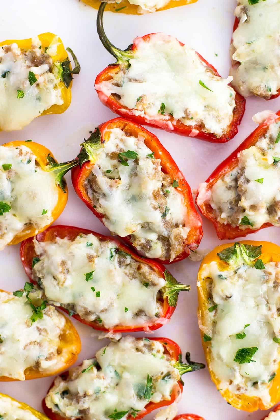 Sausage stuffed mini peppers on a serving plate sprinkled with fresh herbs