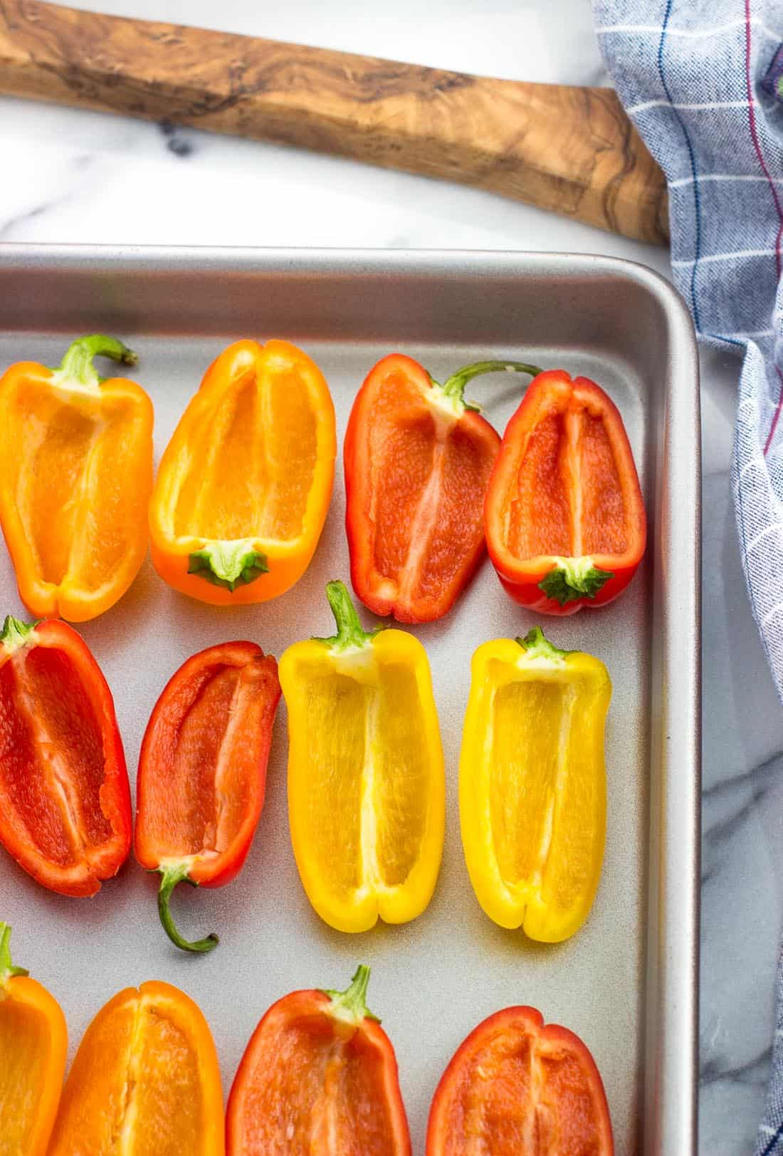 Mini sweet peppers cut into halves with the seeds removed, cut-side up on a baking sheet
