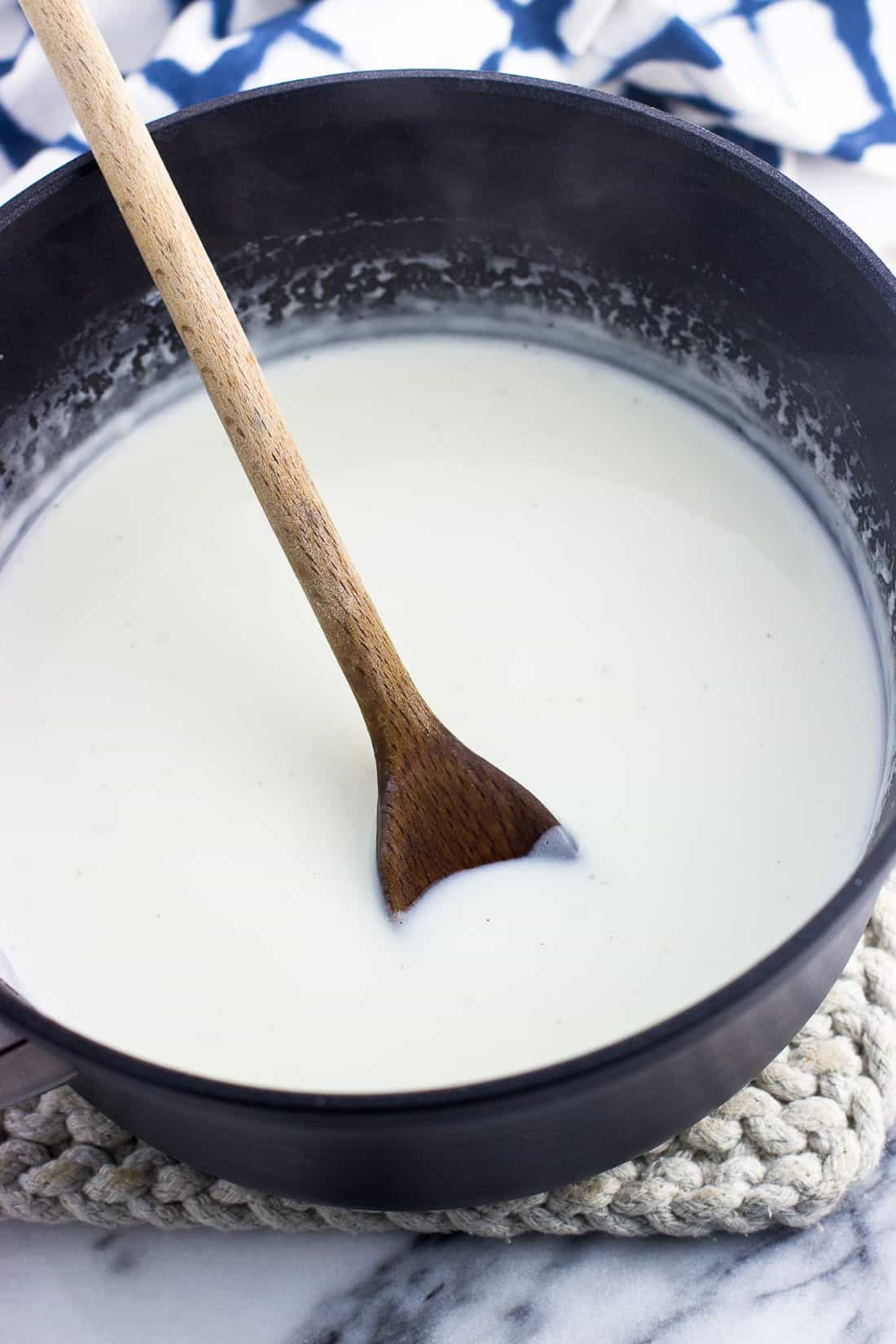 Healthy alfredo sauce in a saucepan with a wooden spoon after thickening