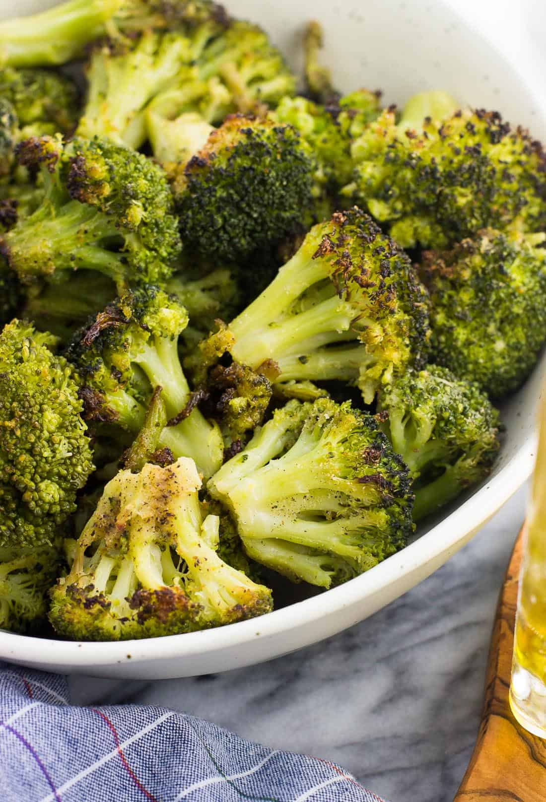 A close-up picture of oven roasted broccoli in a serving bowl