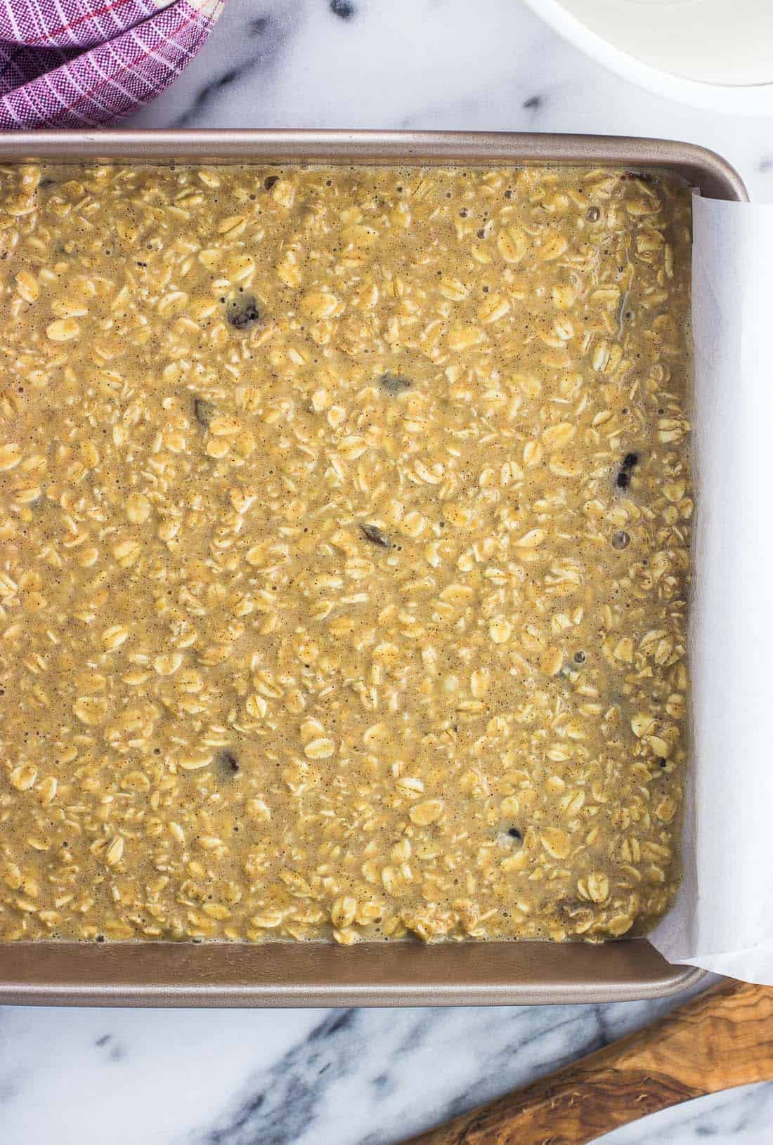 Peanut butter baked oatmeal in a parchment-lined pan before being baked