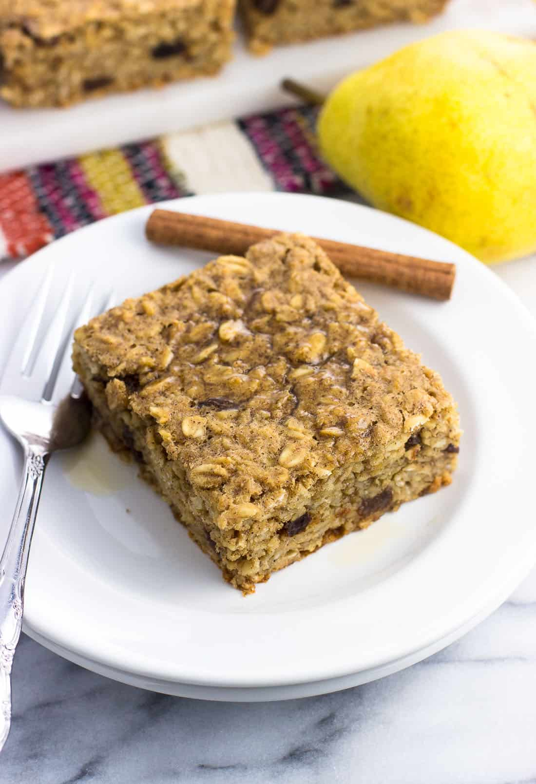 A square of peanut butter baked oatmeal on a small plate with a fork