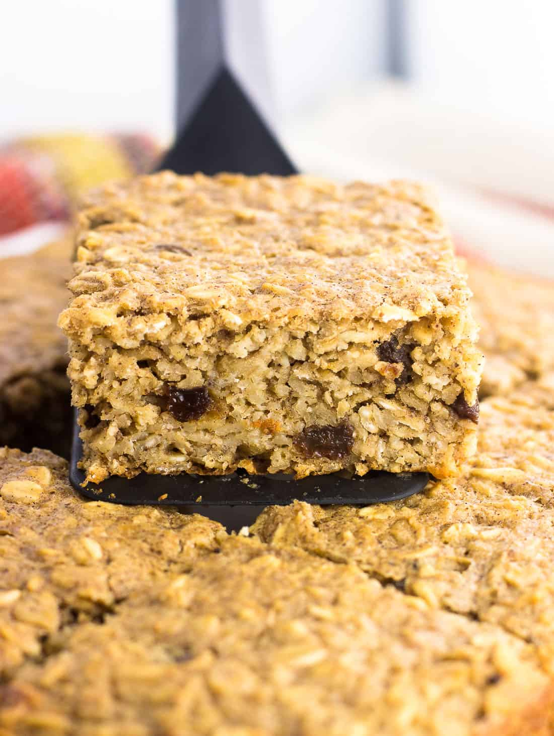 A head-on picture of a slice of peanut butter baked oatmeal being lifted out of the pan