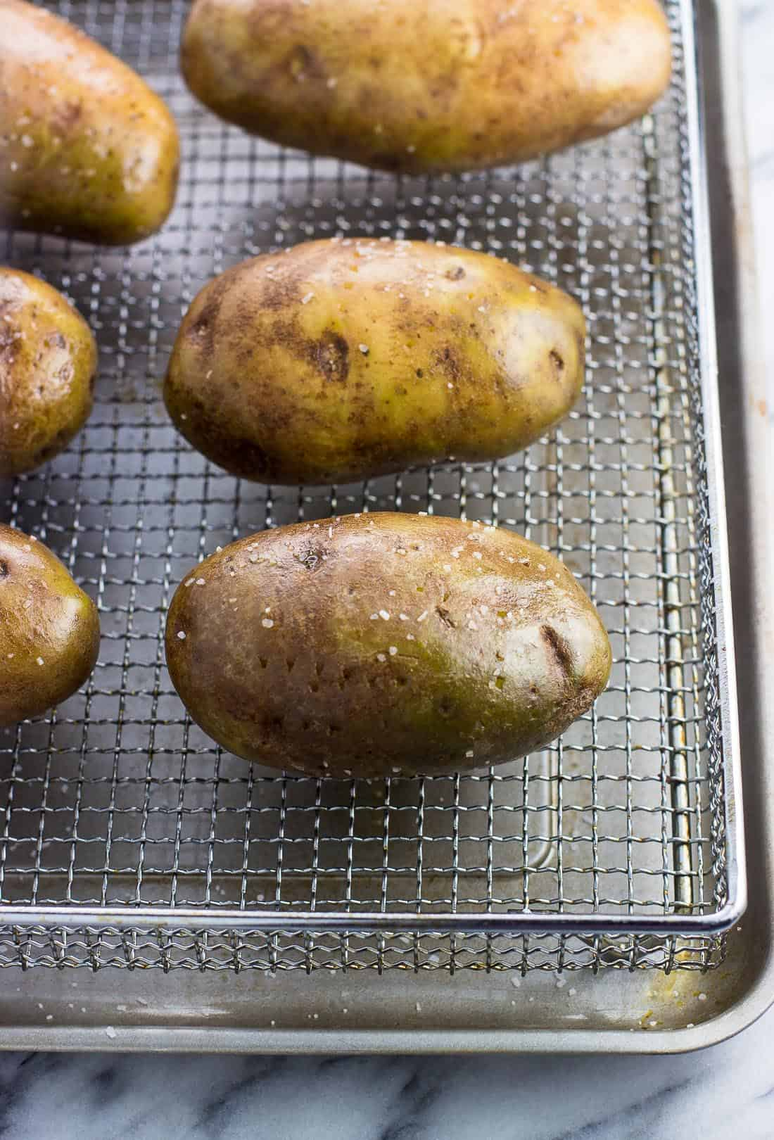 Oiled and salted potatoes on an air fryer basket