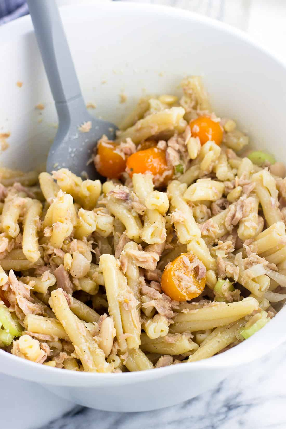 Tuna pasta salad mixed together in a bowl before adding the arugula