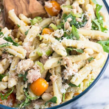 A close-up of a bowl of tuna pasta salad with a wooden serving spoon