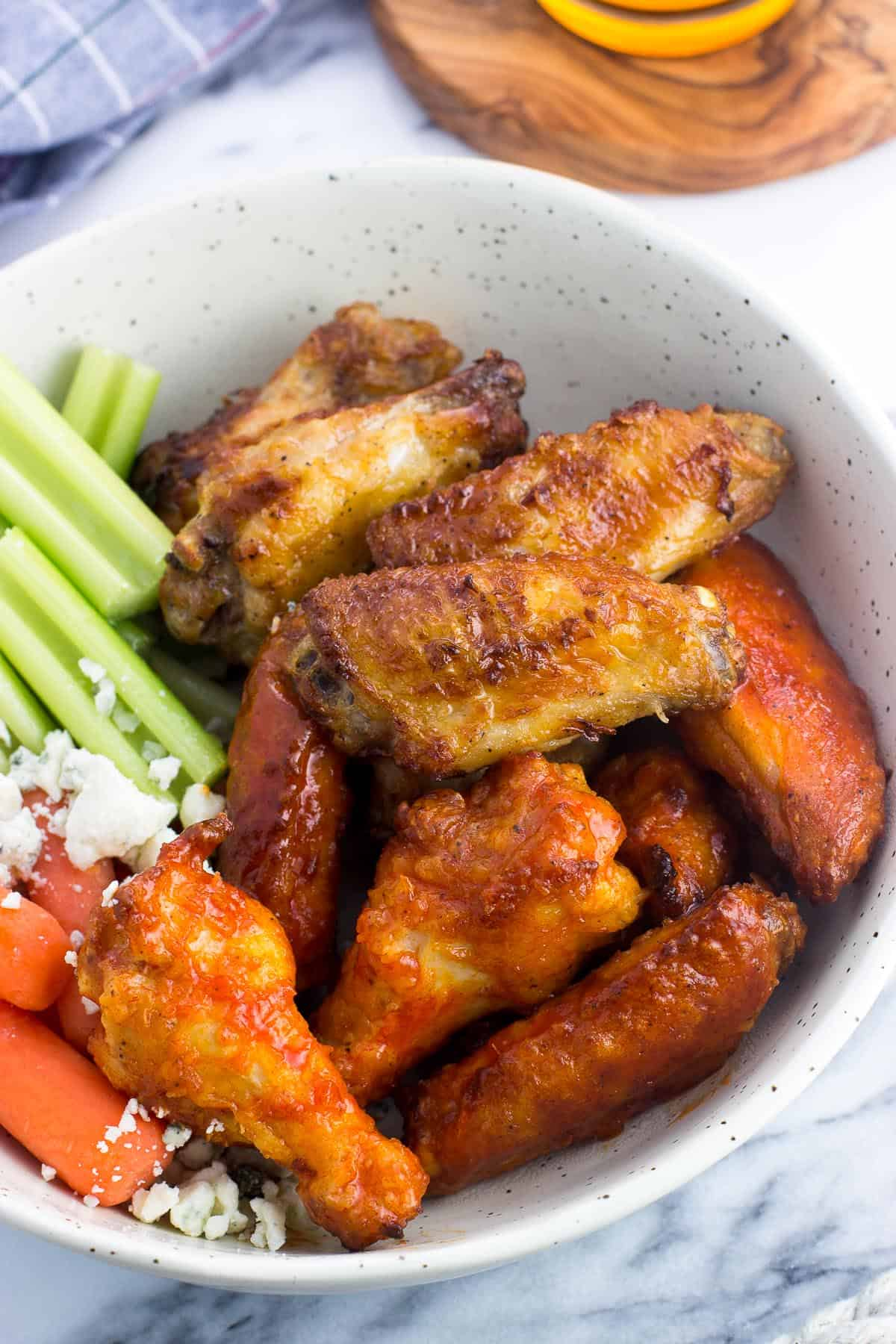 A bowl filled with chicken wings (half plain and half coated in hot sauce) with celery sticks, baby carrots, and crumbled blue cheese