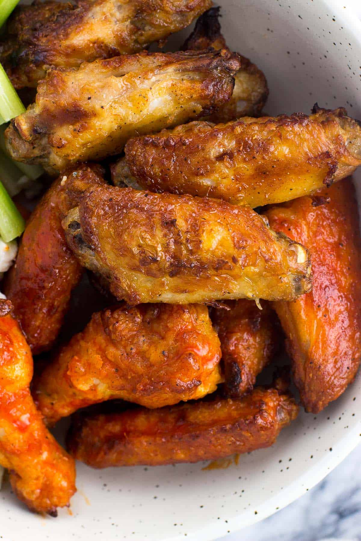 A close-up picture of cooked chicken wings in a dish, half coated in buffalo sauce and half plain