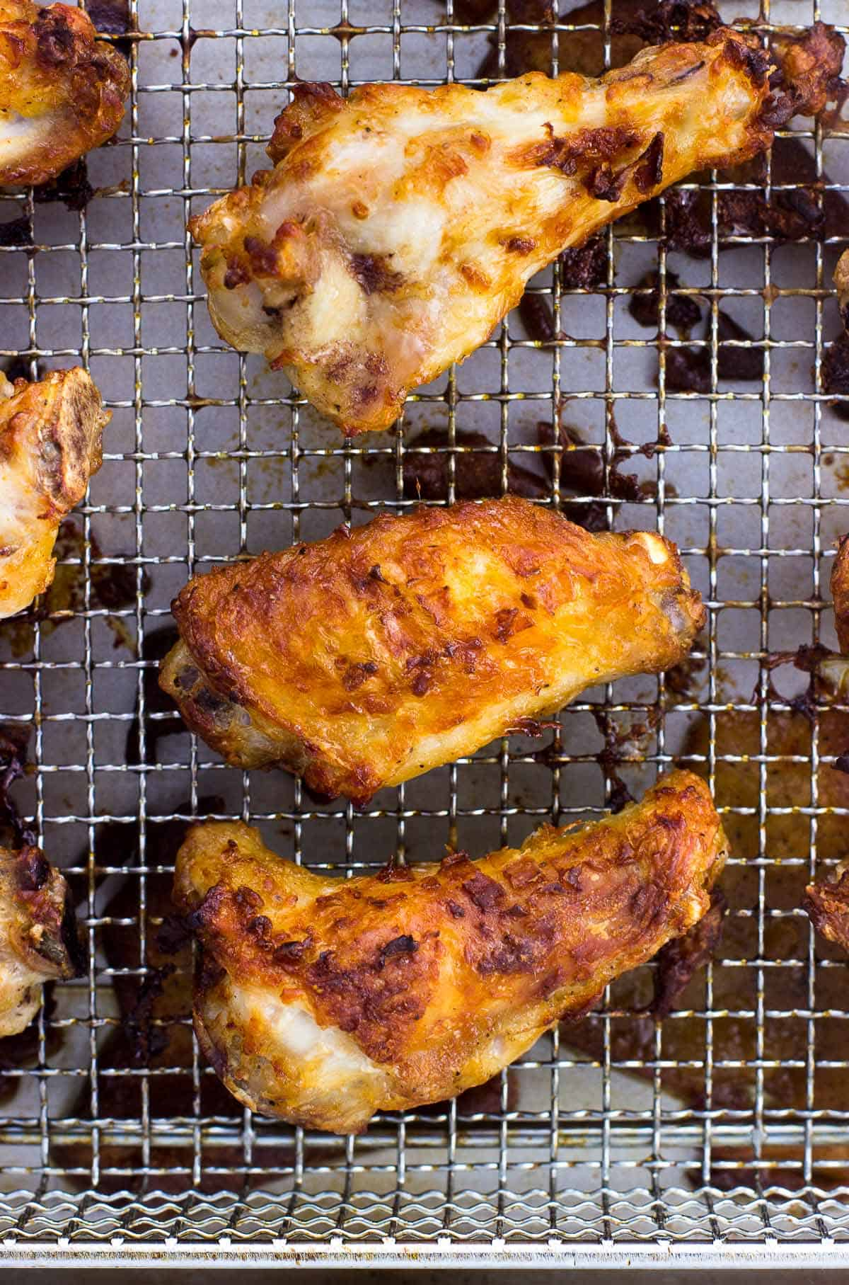 An overhead picture of fully cooked chicken wings on a metal air fryer basket