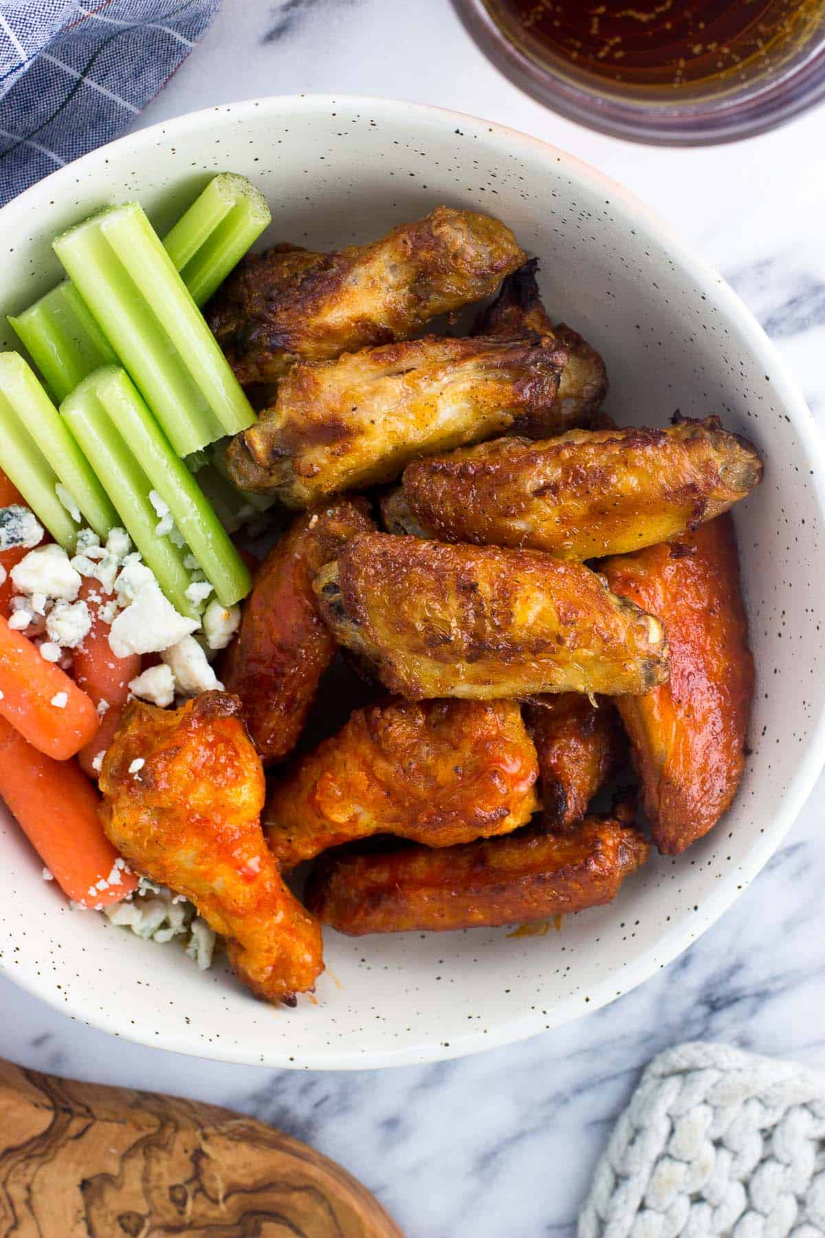 A bowl of wings, celery sticks, baby carrots, and blue cheese.