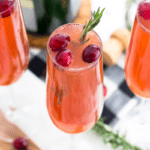 A cranberry mimosa in a champagne flute garnished with fresh cranberries and a sprig of rosemary