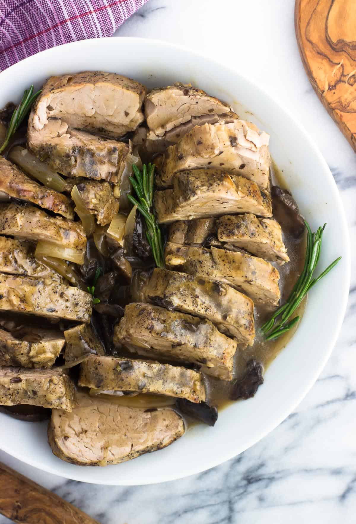 Sliced pork tenderloin in a serving dish with sauce and rosemary sprigs