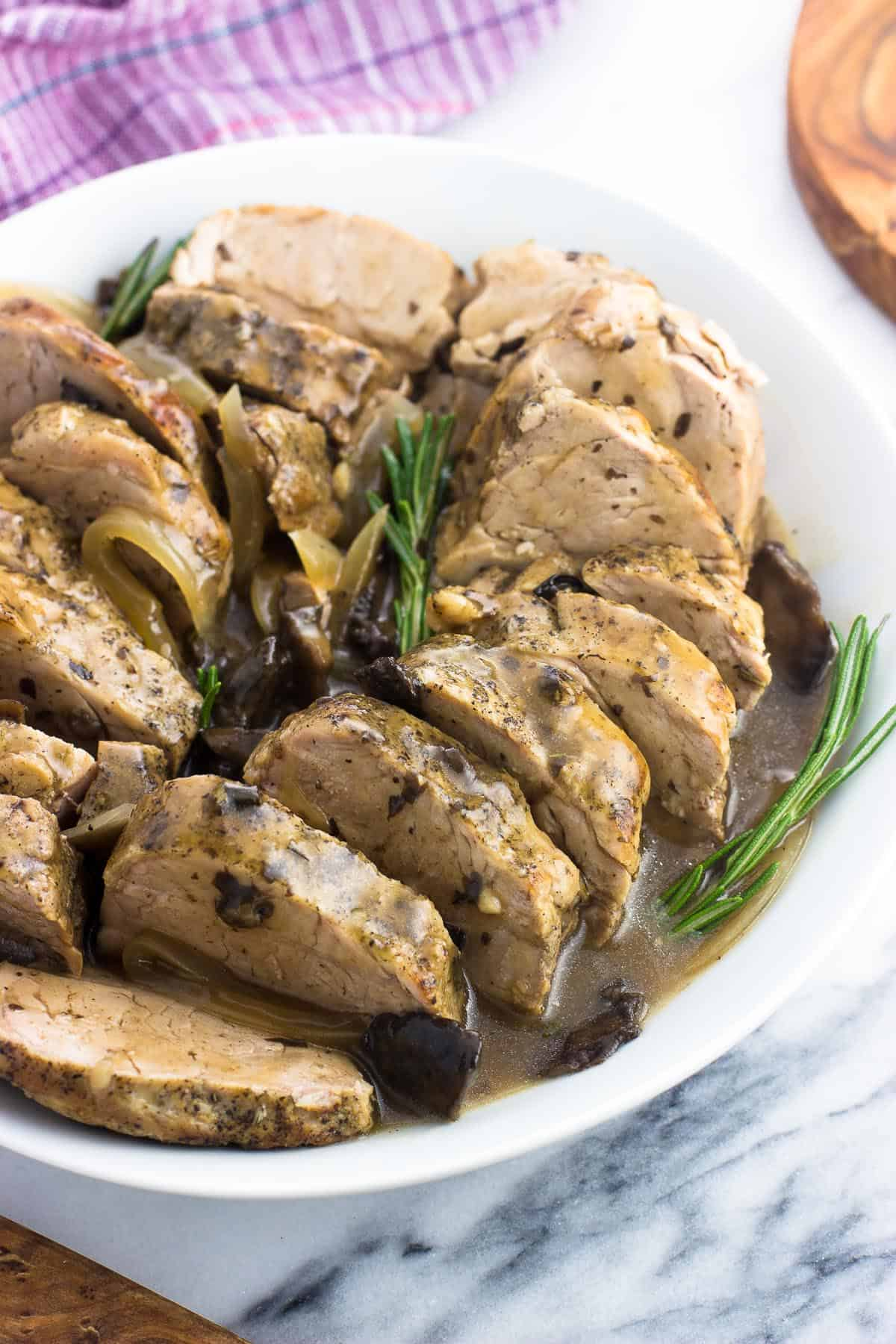 Sliced pork tenderloin in a serving dish garnished with sauce and fresh rosemary sprigs