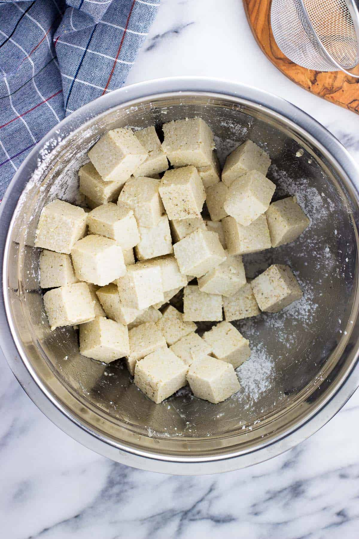 An overhead picture of tofu cubes tossed in cornstarch and spices in a metal mixing bowl