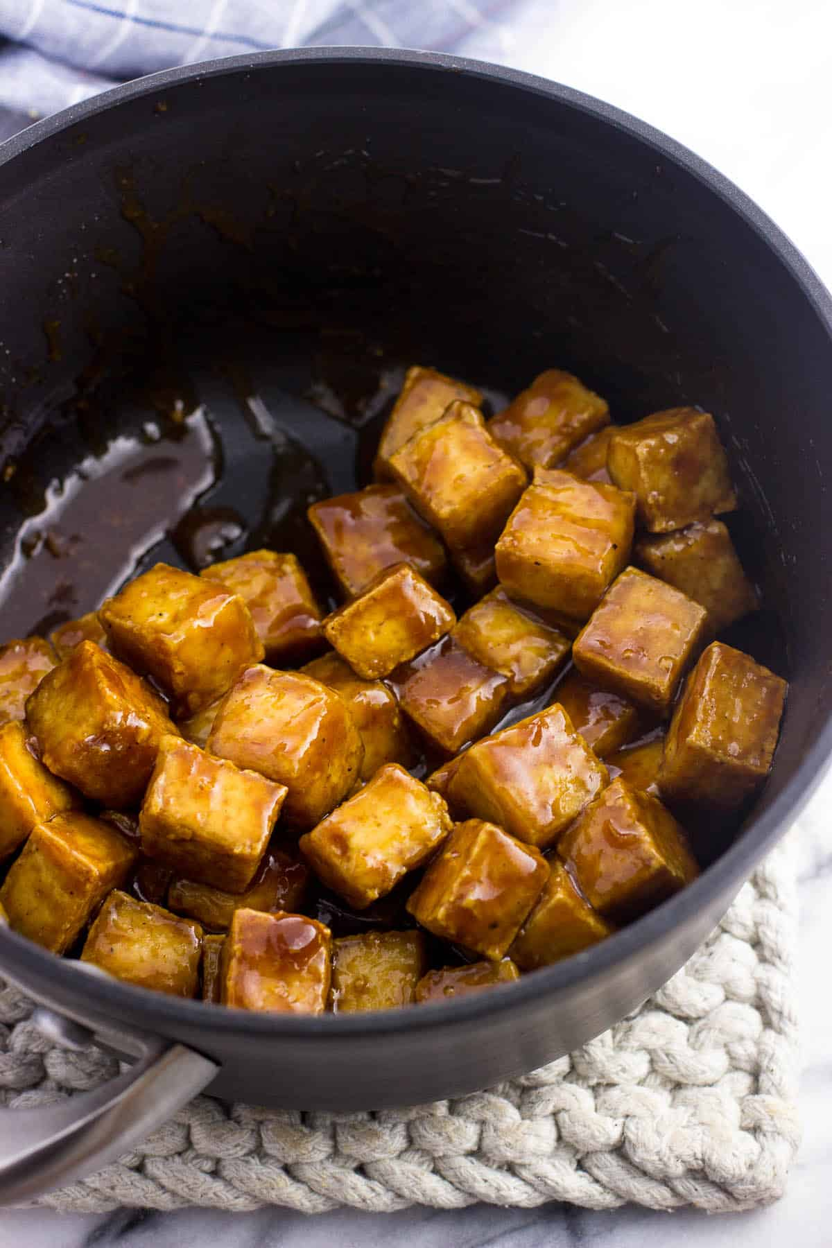 Cooked tofu cubes in a medium saucepan tossed in glaze