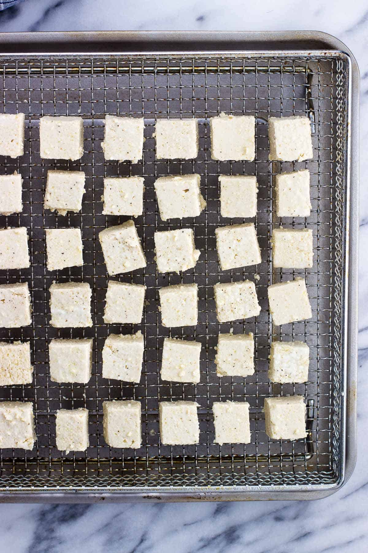 An overhead picture of tofu cubes lined up in a single layer on a metal air fryer basket