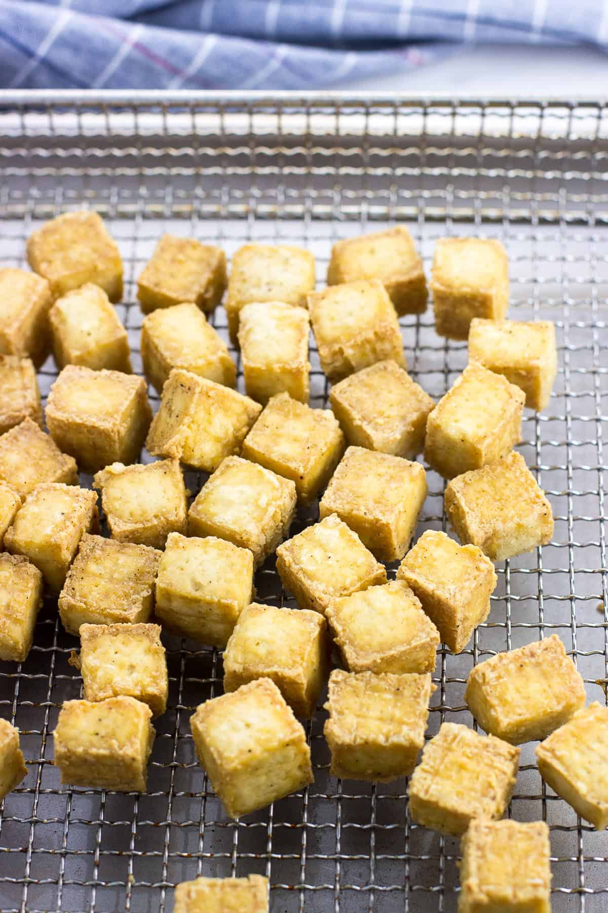 Air fried tofu cubes on a metal air fryer basket