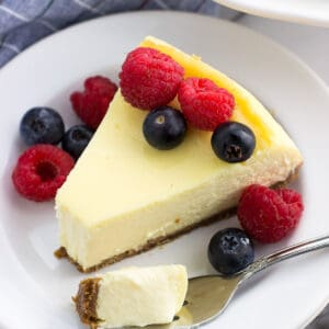 A slice of cheesecake on a plate toped with mixed berries with a forkful of cake next to it