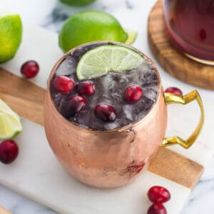 A frosty copper mug of a moscow mule garnished with fresh cranberries and a lime wedge