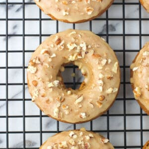 An overhead shot of a pumpkin donut garnished with maple glaze and chopped pecans
