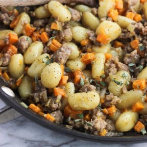 Gnocchi, crumbled sausage, diced sweet potatoes, and sage in a skillet