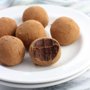 Six chocolate truffles on a small dessert plate, with the front truffle having a bite taken out of it
