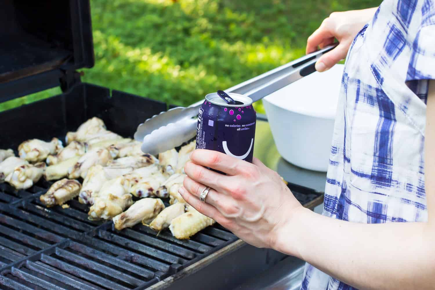 A woman cooking wings on a grill holding a can of water.