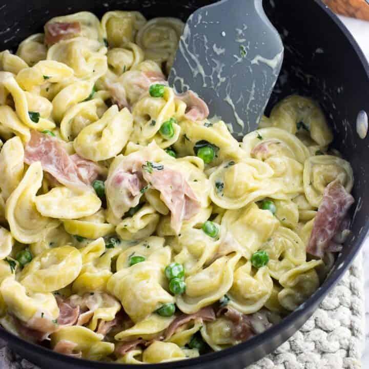 Tortellini in cream sauce with prosciutto and peas
