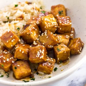 Cubes of tofu tossed in glaze and topped with sesame seeds in a shallow dinner bowl with brown rice