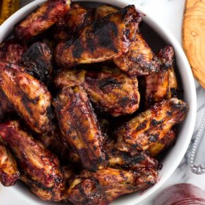 A serving bowl filled with grilled chicken wings next to a glass jar filled with BBQ sauce