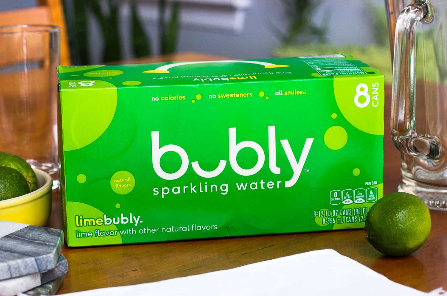 A package of lime bubly™ on a wooden table surrounded by cloth napkins, limes, coasters, empty glasses, and an empty serving pitcher