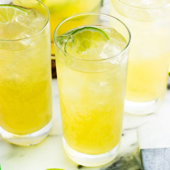 Sparkling mocktails in three tall glasses filled with ice and lime wedges