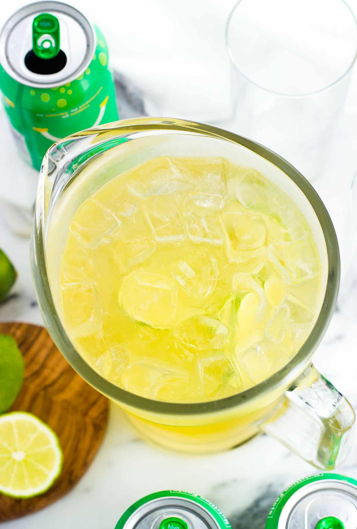 A glass mocktail pitcher filled with ice and next to cans of bubly and cut limes.