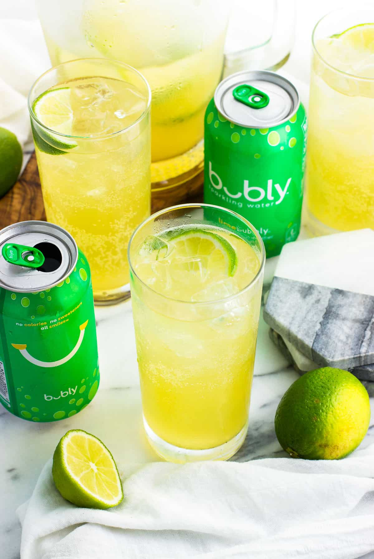 Mocktails in tall glasses next to a glass pitcher, limes, a stack of coasters, and two lime bubly™ sparkling water cans