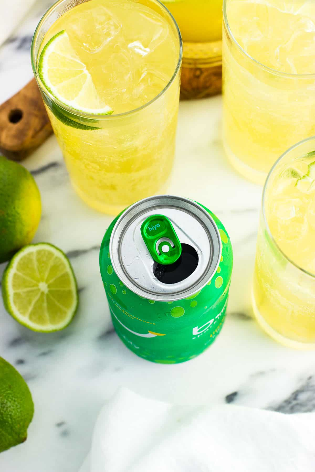 """A close-up of an open can of lime bubly™ with """"hiya"""" printed on the tab surrounded by glasses of mocktails and limes"""
