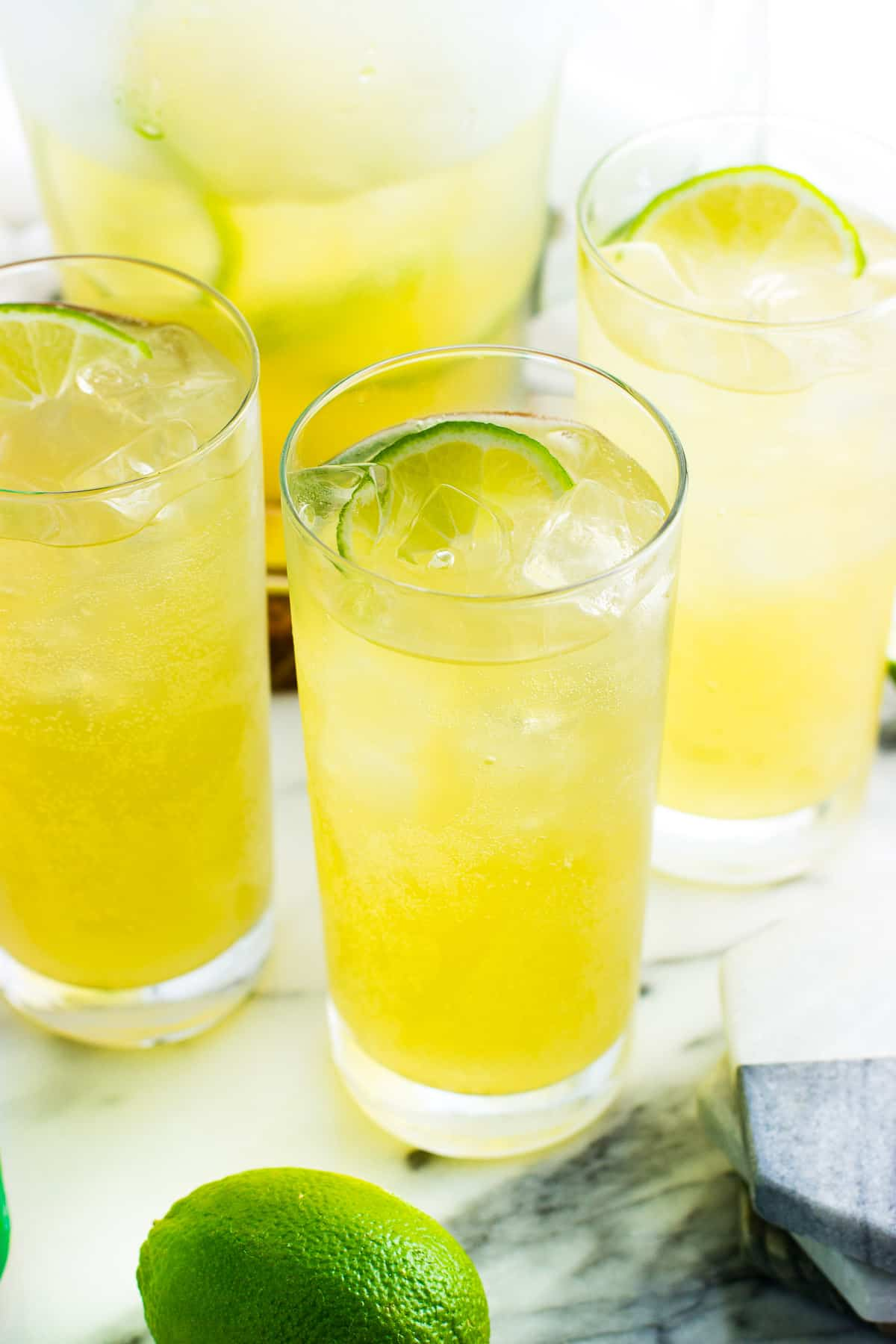 Mocktails in tall glasses with a half-full pitcher, fresh limes, and a stack of marble coasters