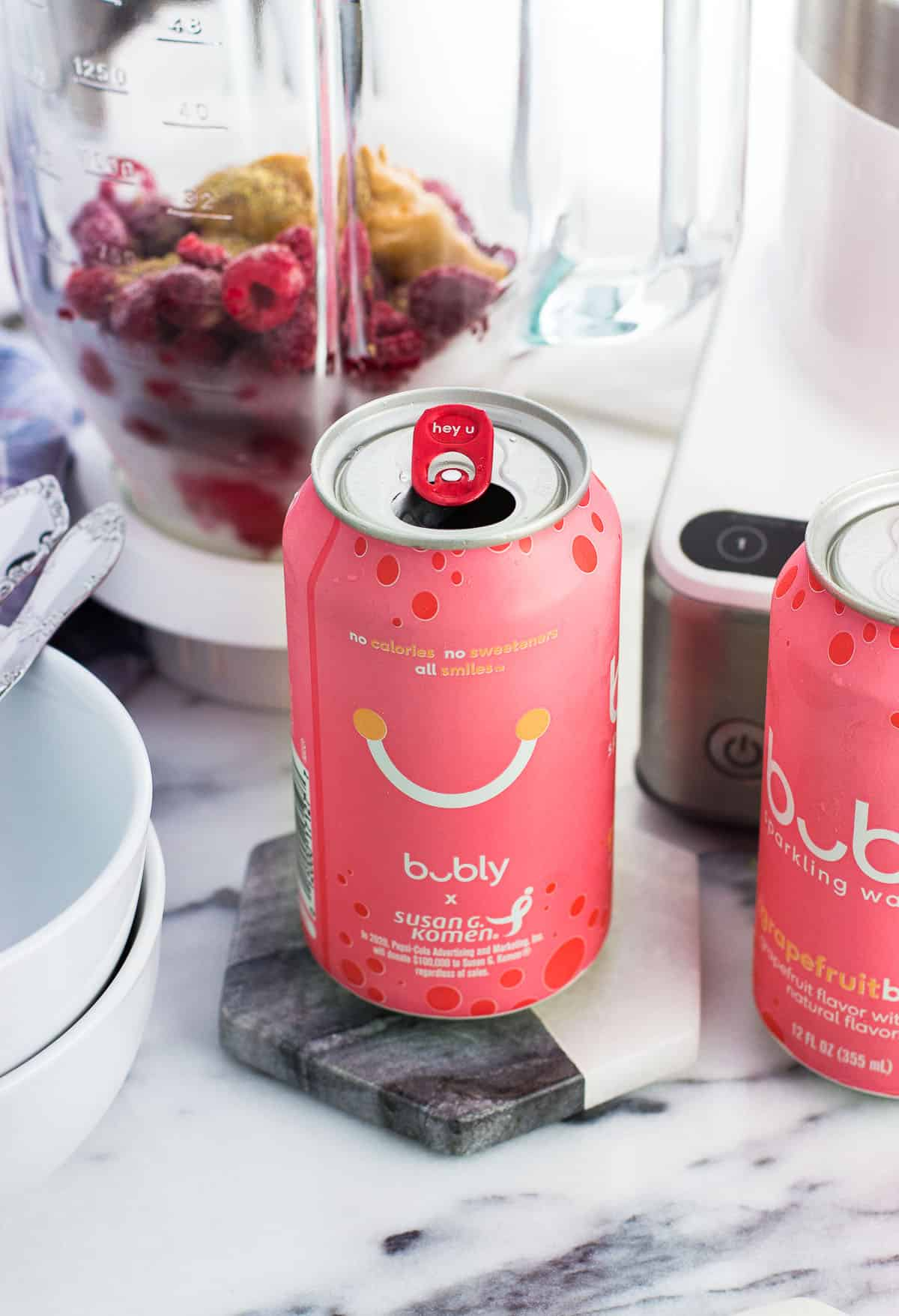 An open can of grapefruit bubly™ sparkling water on a marble coaster next to bowls, another can, and a glass blender filled with the recipe ingredients