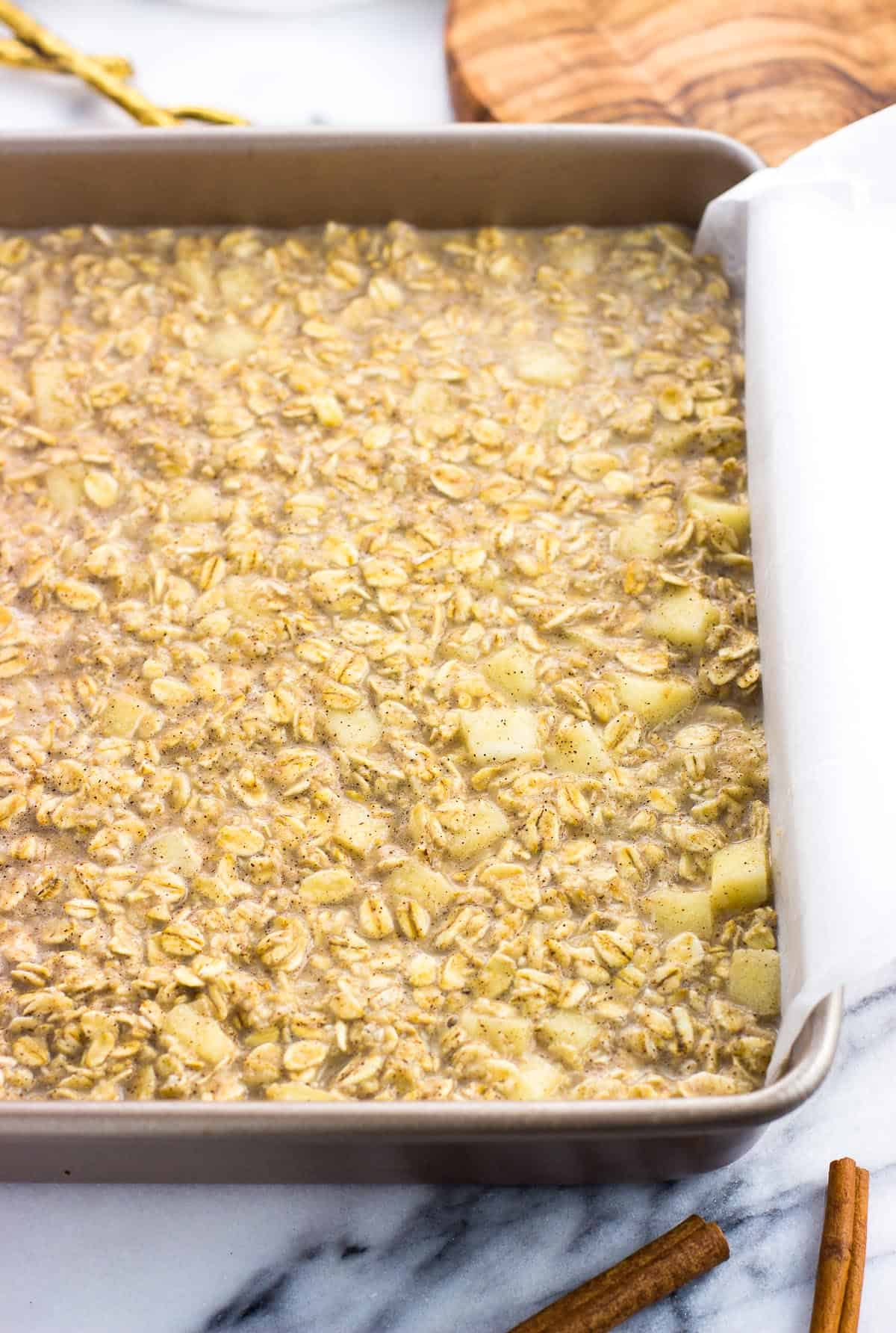Baked oatmeal mixture poured into a parchment paper-lined square baking dish.